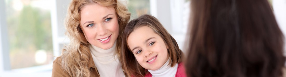 Woman and her daughter looking at a woman smiling